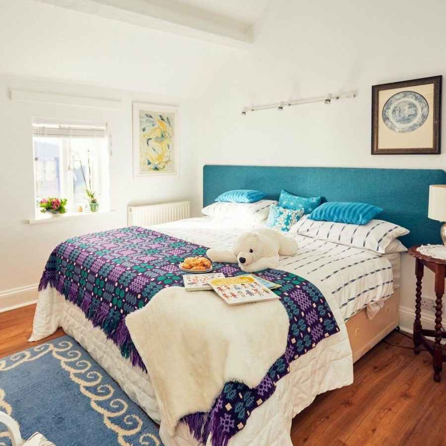 Applebough cottage bedroom showing superking bed with cuddly toy, blankets and blue headboard