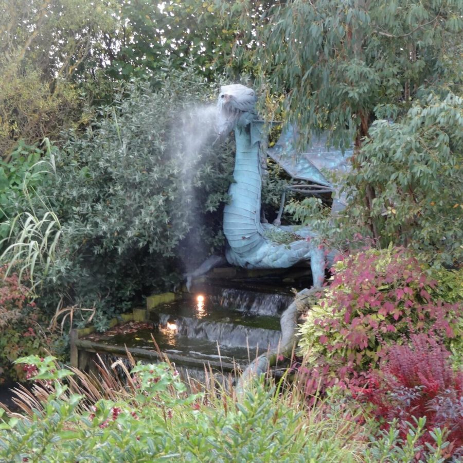 Dragon statue surrounded by plants and trees