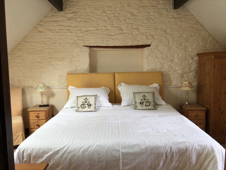 Drakes Room with double bed and cushions. white bedding and wallpaper
