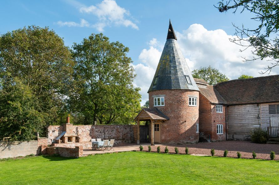 Hop Kiln with cylinder shaped farm building with pointed roof set in gardens