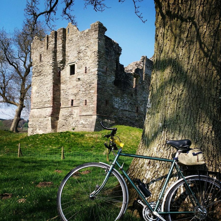 Hopton Castle ruins with cycle leaning against a tree