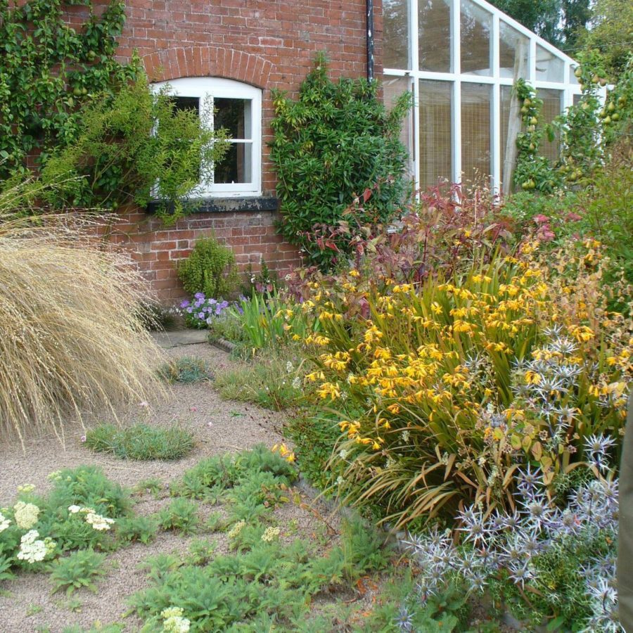 Ivy Croft Garden with house and sun room with planting in front