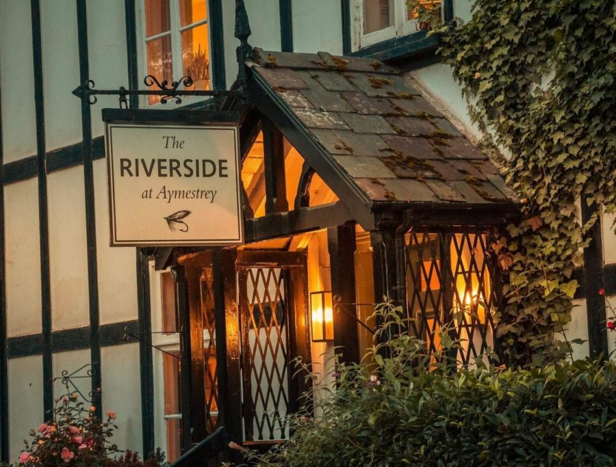 Riverside Front entrance, pub sign with the Riverside written on hangs above door.
