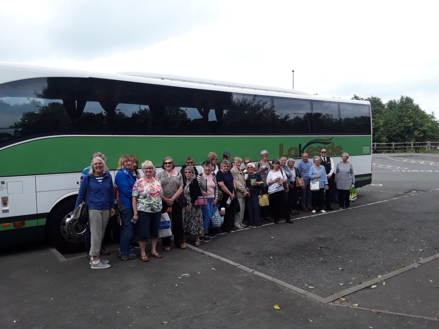 Green and White Coach with group of tourists smiling outside
