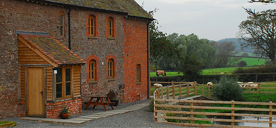 Grafton Farm Outside showing grey and red bricked building and countryside in background