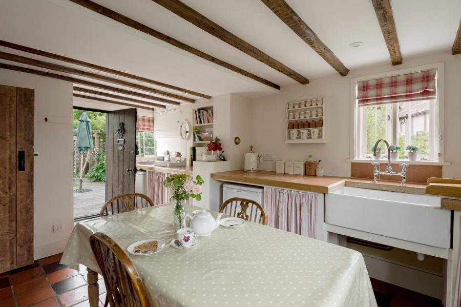 Kitchen with dining table and wooden beams on ceiling