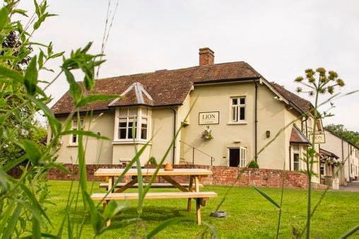 The Lion at Leintwardine pub from the garden. Showing grass and picnic bench