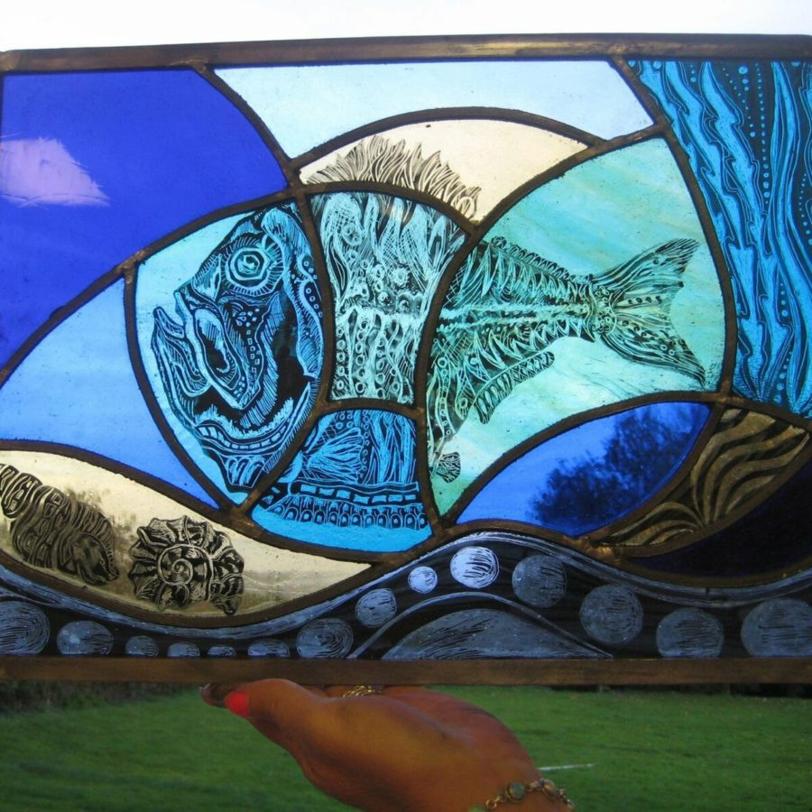 Stained Glass with shades of blue and fish image. Held up against countryside backdrop