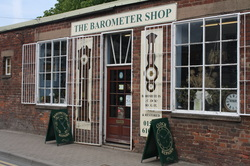 front of The Barometer Shop building. With signage and large windows
