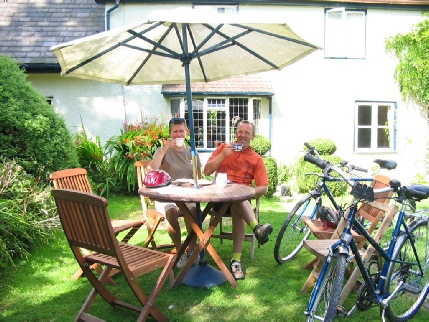 two cyclists enjoying a break on a table and chairs with sun umbrella, two bikes leaning