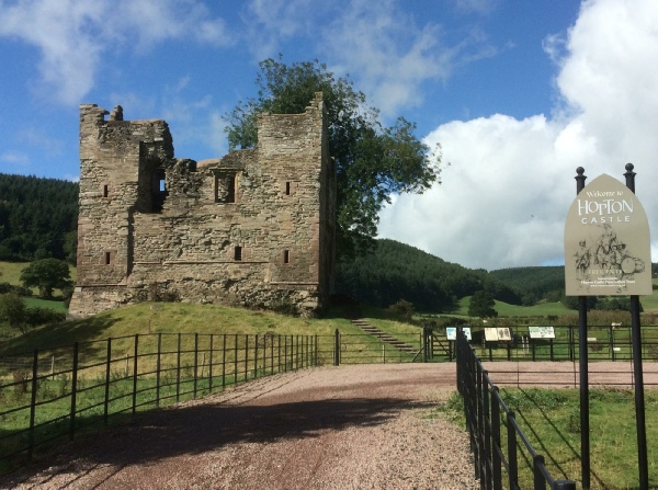 Hopton Castle with ruined stone castle with driveway and fencing