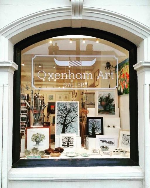 Oxenham Arts Window display with artwork with trees and branches, logo on window