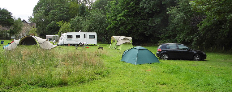 Camping site with blue and green tents, cars and a caravan