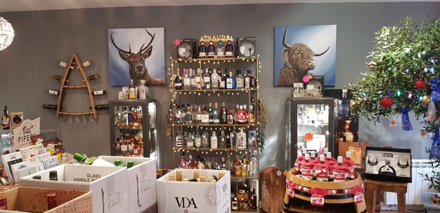Internal Shop image with bottles of spirits on wooden shelving.