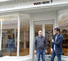 War and Son shop front, with shop owners in front of door. Military uniform on display in large window