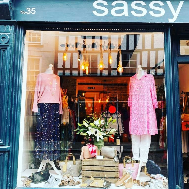 Window Display with pink outfits on mannequins with bags and shoes. Blue shop front with large window